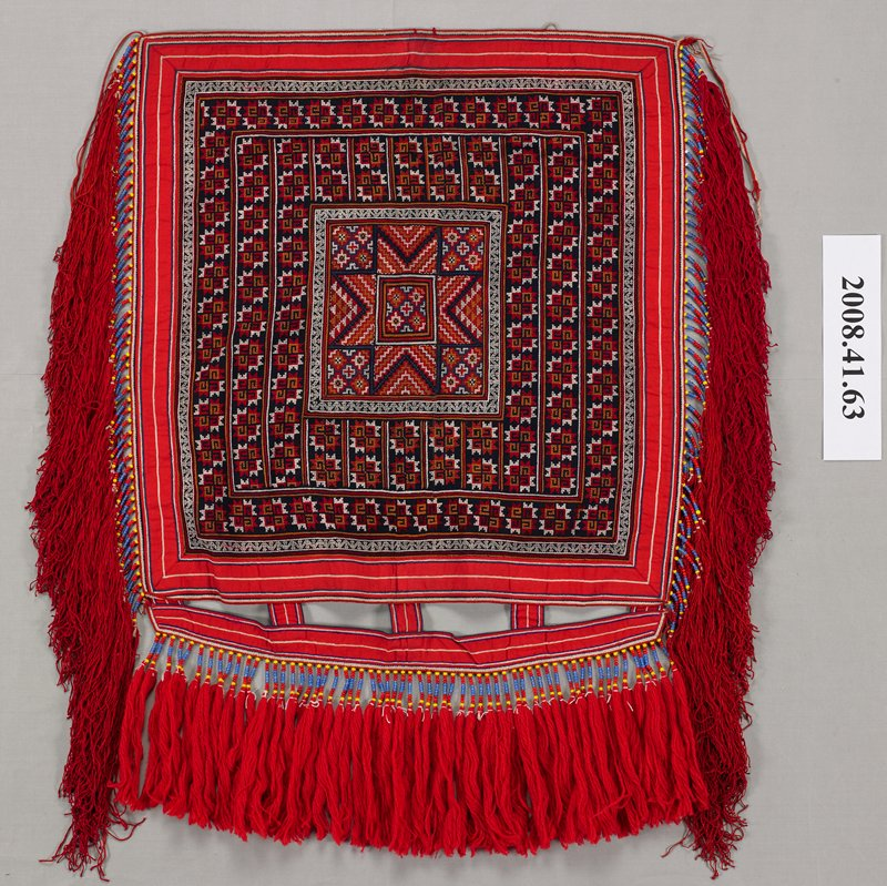 embroidered square with red striped border with tabs on one side; center square with eight pointed star; predominately cross stitch in mostly white, rust, red and orange; red, blue and yellow beads with attached red tassels on three sides; silk tassels on two sides; wool (?) tassels on one side