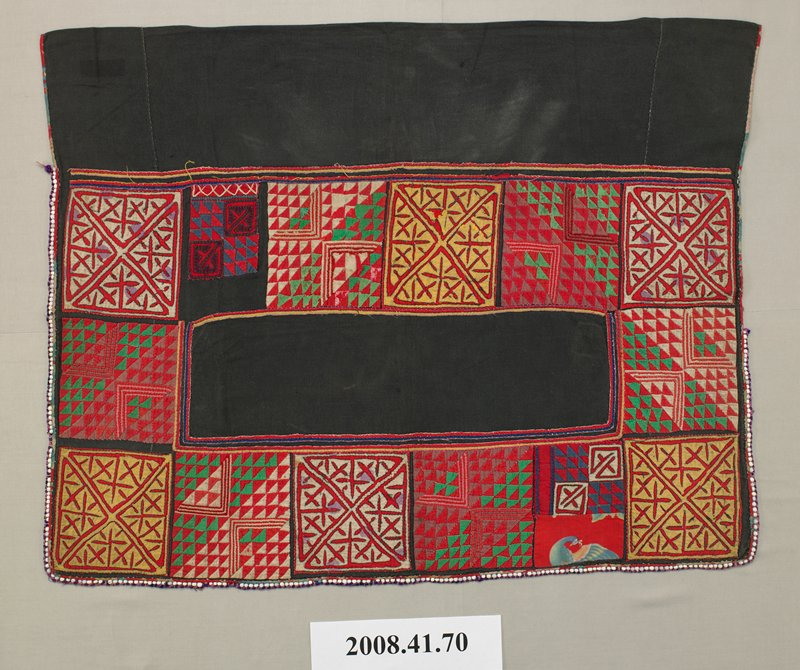 rectangular area of appliquéd squares around black fabric rectangle; plain black fabric panel across top; alternating appliquéd squares--small red, green and white triangles and larger triangles with cross motifs in red, gold and white with purple dots; trim with beads and purple thread on bottom and part of two sides