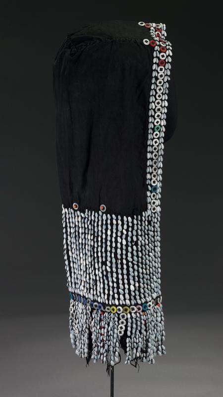 hood-like garment; black, with thick twisted black fringe; sides and bottom decorated with light blue shells, and shell and shell and bead fringe; predominately white buttons accent top; white button fringes; red beads