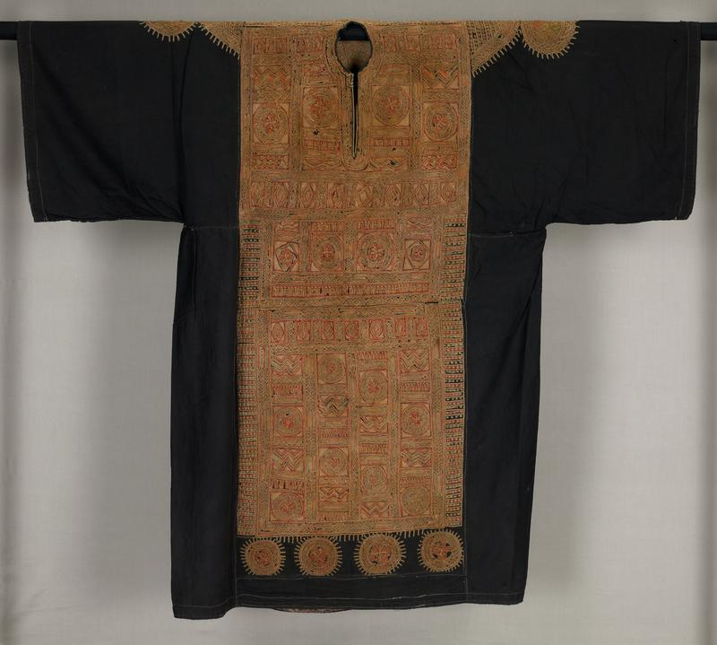 """wide sleeved black dress with embroidered panel from shoulders down to four separate embroidered medallion shapes near hem; panel in three sections (chest, waist and apron) embroidered in rust red, pale orange and gold threads in geometric, circle and border patterns; back panel from shoulder to waist with """"V"""" pattern and medallions incorporated in overall panel; triangular and circular embroidered areas at top of sleeves; small straight opening at neckline"""