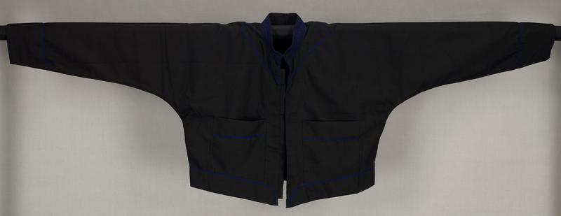 black; short; long sleeves; no closures; band collar; two front pockets; blue stitching at and around collar, at top of pockets, around sleeve cuffs and at bottom
