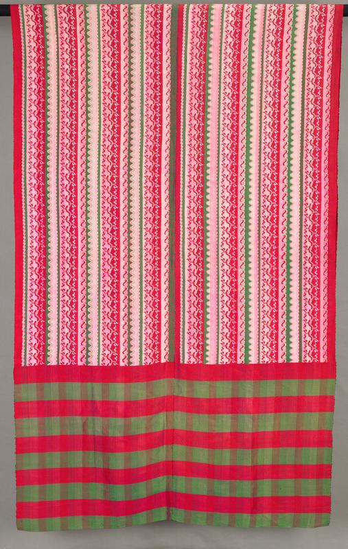 red, green, pink and grey; red and green plaid at ends; central section woven with bands of curvilinear designs and wave shapes; two panels sewn together