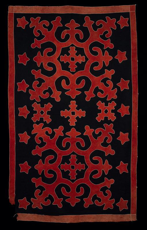 black and rust felt rug with white cording around all cut edges; geometric design includes stars and organic shapes