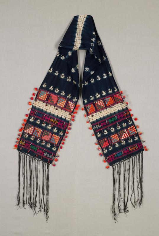 indigo colored headpiece with white floral motifs and blue and white stripe pattern; ends each have two bands of appliqué and two bands of multicolored embroidery, seven rows of tassels, fringe and a row of pompoms along each side