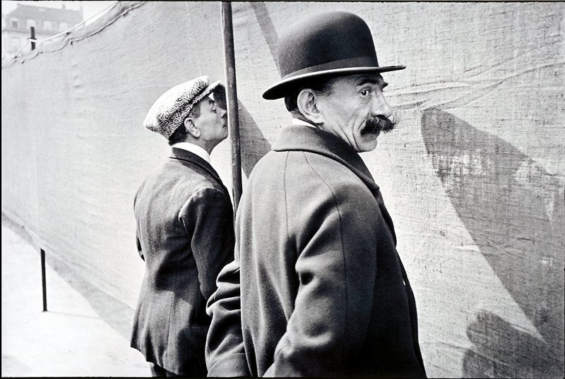 two men in hats trying to look through a cloth fence
