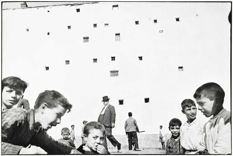 wall with small windows all varying in size and location; group of children are gathered in front of it