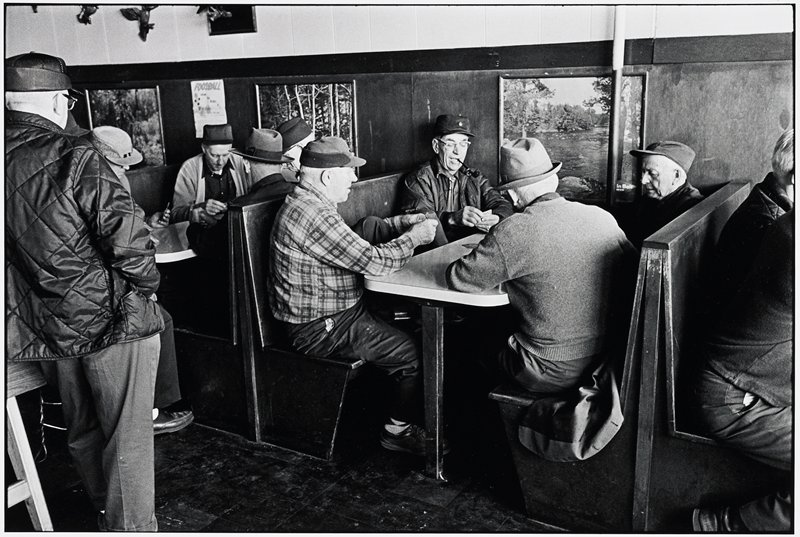 men sitting in restaurant booths, playing cards; all men wear hats or caps; outdoor photographs on wall behind men; standing man at L