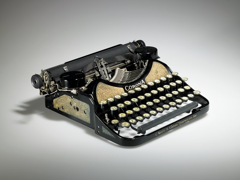 "small manual typewriter; front panel above keys printed in gold: ""CORONA/ PROFESSIONAL"" with gold textured panels on sides; ""C Smith & Corona Typewriters Inc."" on front panel below space bar"