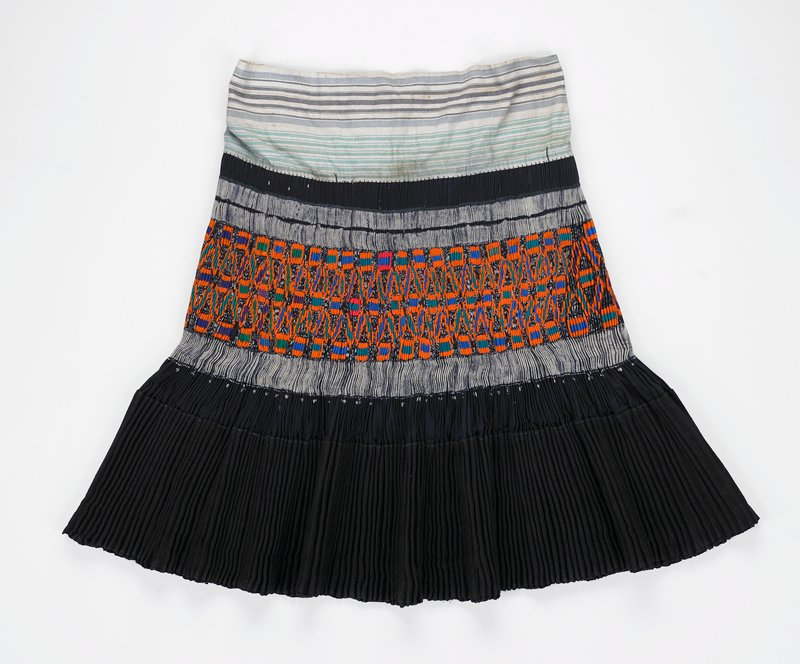 pleated skirt; horizontal striped waistband with tan, blue and green stripes; top section is blue (indigo?) with two narrow blue and white stripes above appliqué and a wide blue and white stripe below; appliqué in orange, green and blue geometric shapes; fabric under appliqué is dark blue with white pattern; lowest section of skirt is heavy black fabric in two layers