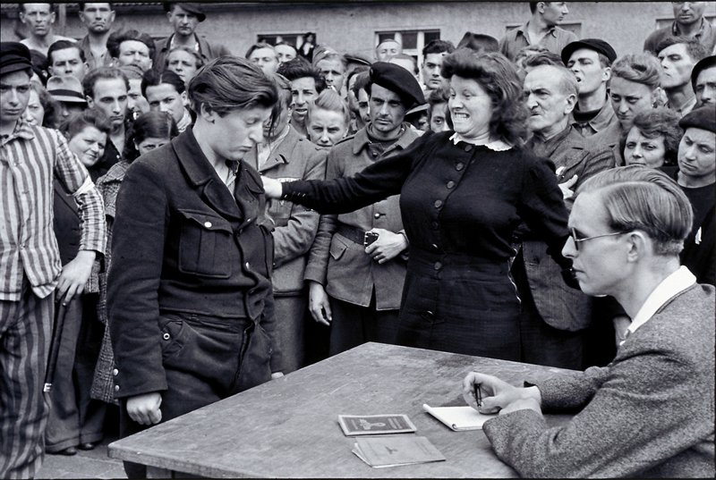 woman standing in front of table with seated man, with crowd surrounding them