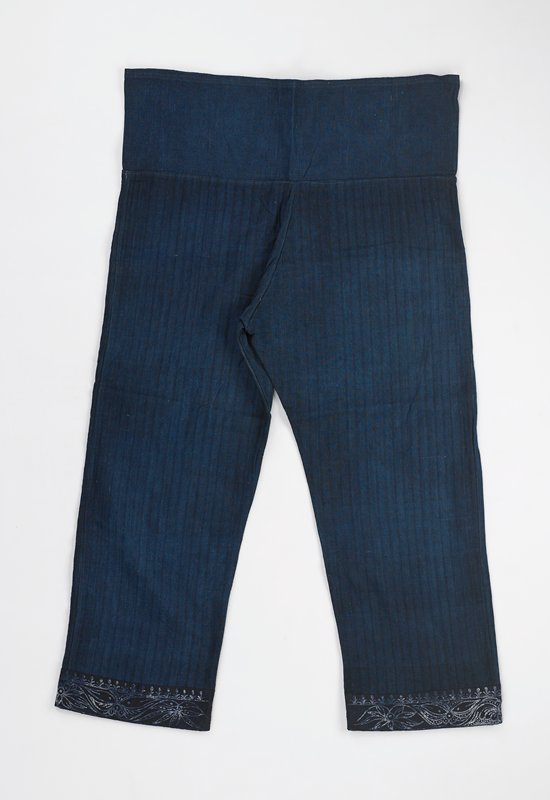 batiked cotton women's dark blue trousers; deep waistband of solid blue denim-like fabric; trouser legs of dark blue with black striped fabric; bottom cuff of dark blue with white design; batiked cuff pattern with top border row of flowers and larger wavy flowered design under flower row