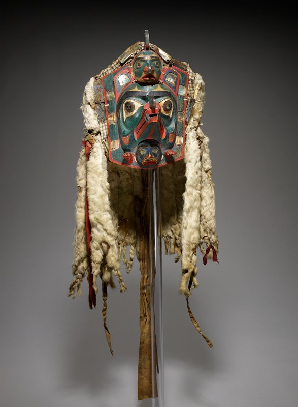small, roughly rectangular mask of bird's head with long bead with four abalone teeth; two small frowning human faces above and below bird's head; lower face also has two hands; human faces have abalone inlay eyes; bird's head has abalone and copper eyes; red, green, black and white pigments; ermine pelt pendants hand down sides and back; ermine pelt around cap; tan and brown plaid fabrics behind mask and on crown; wool, ribbon and printed cotton ties and pendants