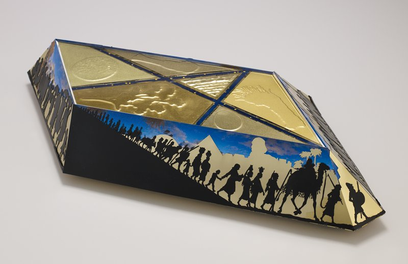 parallelogram shape with beveled sides; two squared-off corners; top surface has three triangular shapes and two other shapes in gold with hammered designs of pyramid, egg and organic shapes; sides have procession of figures (cutout black silhouettes) before layered gold skylines and landscape shapes (including Statue of Liberty) with printed tin sky behind; printed tin pieces on underside, with center piece having carpet design