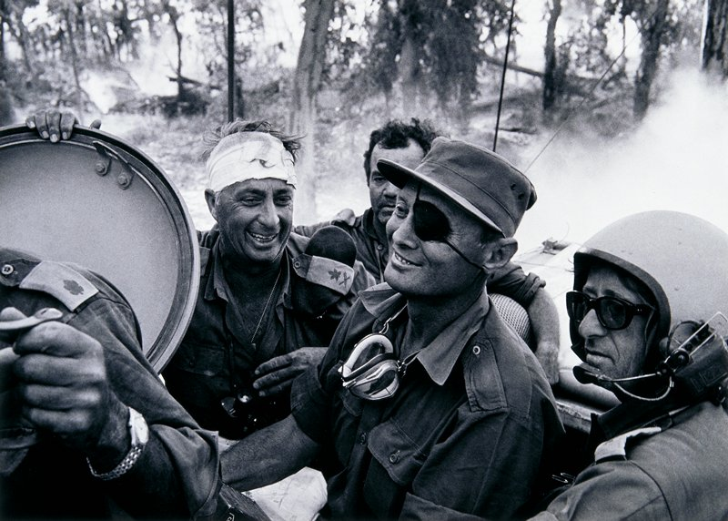 smiling soldier wearing an eyepatch at center with three other men surrounding him; man at lower right corner wearing a helmet and dark glasses; man at left of center with bandaged head