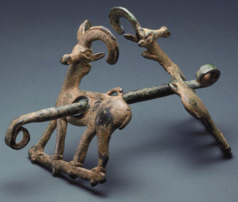 bit and cheek plaques; rigid mouthpiece of round section, flattened at each end and rolled into spiral rings to which reins were attached; cheek plaques in form of standing ibexes whose bodies are in profile relief with heads affronted and modeled in the round; on back of plaques are two protruding pins and two loops for fastening split strap of bridle; horn of one ibex broken off and missing; bronze