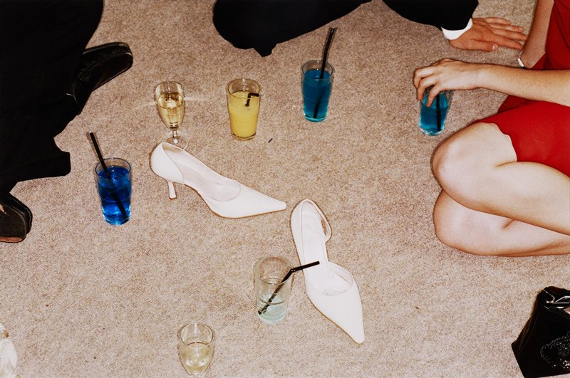 legs and hands of two men and one woman seated on a tan carpeted floor; various drinks in tumblers and wine glasses on floor; pair of woman's white high-heeled pumps on floor at center