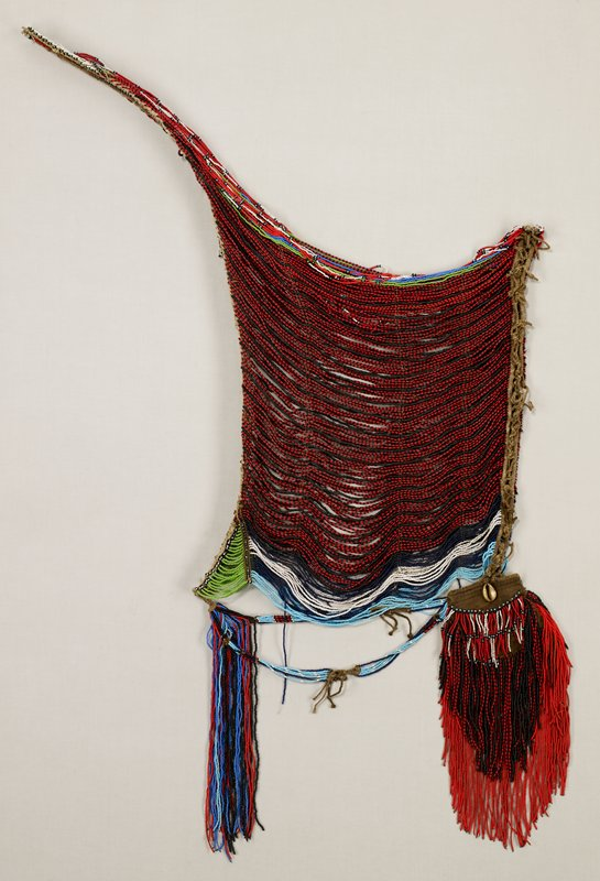 "strands of red and black beads attached to central bars of cloth-covered metal with ties; rigid, arcing thread-covered bar with bead strands between (white, black and red) on back; pouch-like bottom element in front of brown cloth with black, red and white beaded strands with some highlighting blue beads; tassel of blue, black and red beads on back; cowrie shell at front top of ""pouch"""