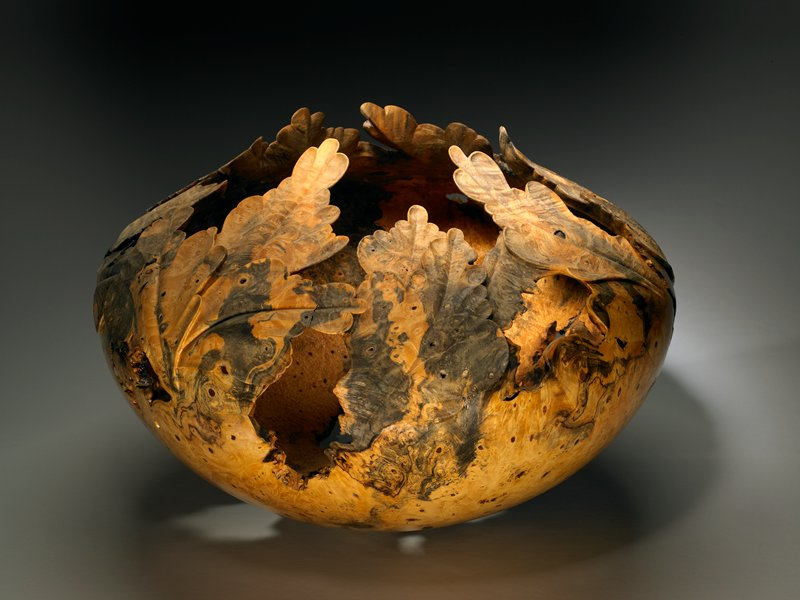 turned and carved; large rounded bowl form with slightly concave foot; top edge carved into leaf-like forms; tan and grey mottled colors; inherent irregular holes