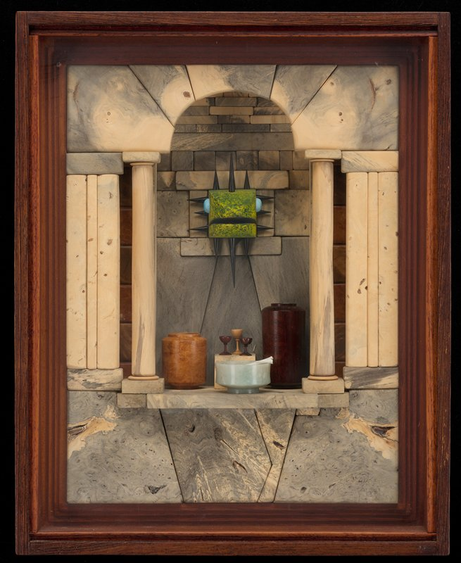 shallow shadow box with columned archway and architectural elements; niche behind archway creating small room with small square table with three goblets, two tall cylindrical containers--the largest containing stones--and a light blue bowl containing bones from a small animal; green dragon's head with blue eyes and black spikes on head, cheeks and chin extending from small opening in back wall