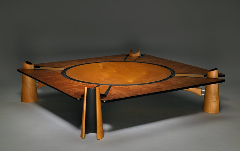 X-shaped stand with four C-shaped open cone feet (black at outer edge/openings); square platter with rounded notches at corners for stand feet; central light-colored circle, bordered in black; four radiating light wood segments, bordered in black, at corners
