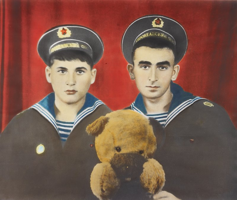 portrait of two young men wearing sailor uniforms with blue and white collars and caps with lettering in gold on front; brown teddy bear held between boys; red ground; white frame