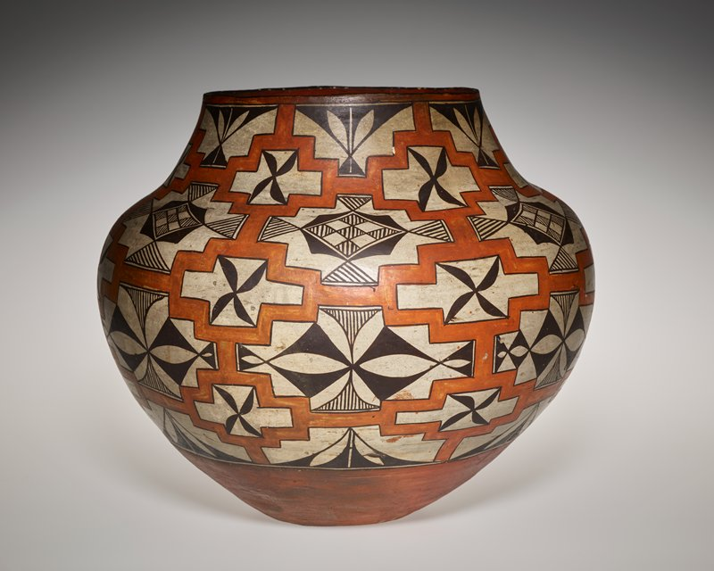 FJS #150; bulbous shape with narrowed rim; stone-rubbed white slip with black designs framed by interlocking orange/ brown pigments