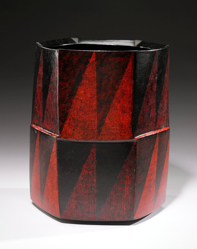 cylindrical shape with slight facets forming rounded hexagonal body; horizontal facets at center; red, black and grey glaze with gridded black and red triangles on exterior, subtle red triangles at interior and grey triangles at top rim and bottom around foot ring
