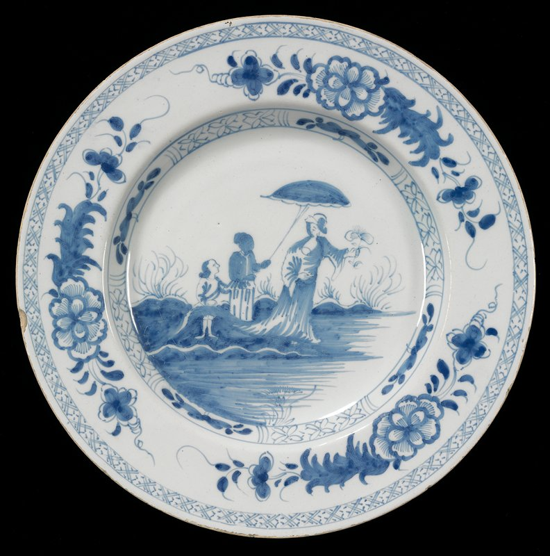 wide rimmed plate; three figures in a landscape; tall figure on right holding flower; center figure holding (sun?) shade over tall figure; short figure at L; floral motifs around rim and between rim and bottom; geometric design around outer edge of rim
