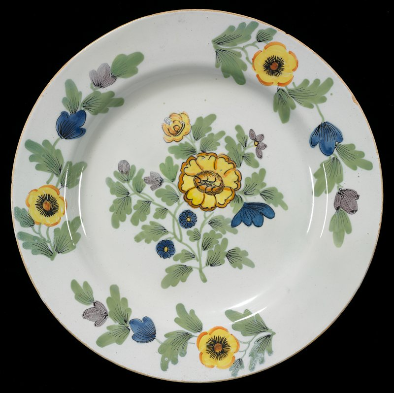 defined rim; foot ring; decorated with central floral spray with yellow, purple and blue flowers; three vining floral sprays around edges of plate; pale blue ground