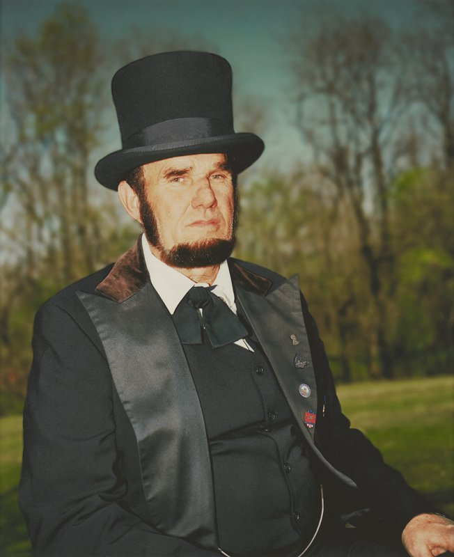 seated portrait of green-eyed, bearded man dressed as President Lincoln; watch chain attached to vest; four pins on PL lapel; blurry trees in distance with darkening blue sky; mounted behind glass in black wood frame; one of a set of 18 photographs to be displayed together