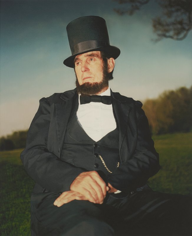 portrait of bearded man dressed as President Lincoln; man seated looking to PR with folded hands resting on PR thigh; image of figure is in sharp focus at top and gets progressively more blurry toward bottom; line of blurry trees with clouds and blue sky in distance; blurry branch in URC; framed behind glass in black wood frame; one of a set of 18 photographs to be displayed together