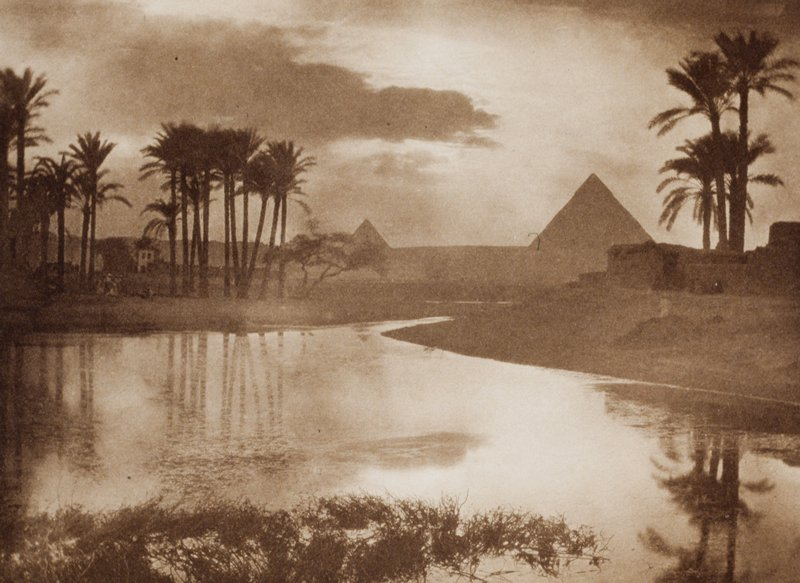 body of water in foreground with palm trees, desert, and pyramids in distance