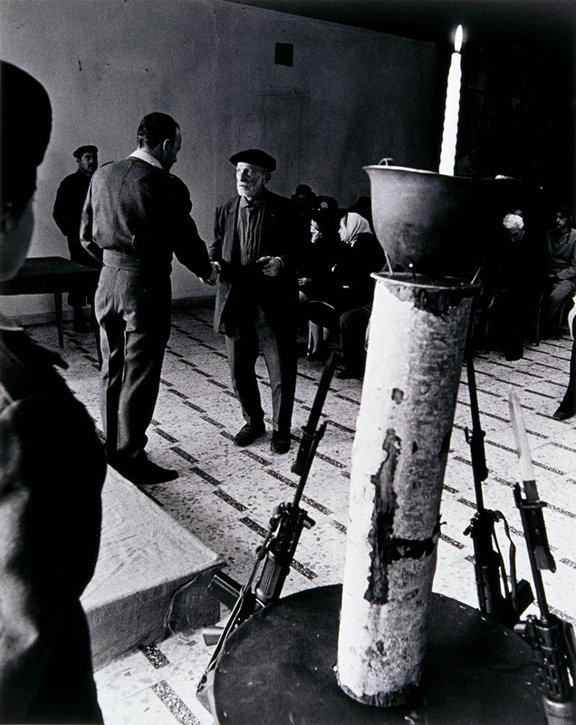 candle burning inside an upturned helmet on top of a log with bayonettes leaning against it at LR corner; two men shaking hands at center