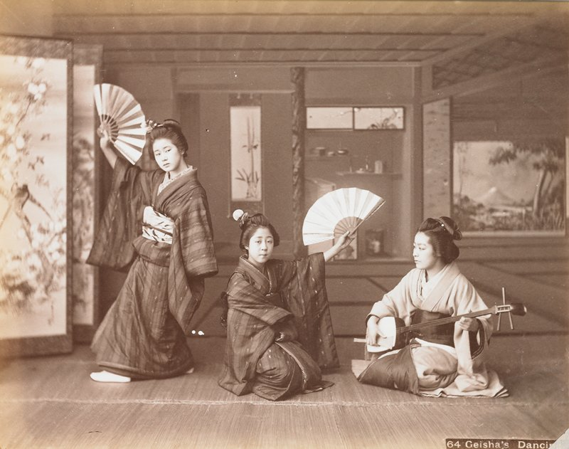 three young women in an interior; seated woman at right plays a shamisen; two other young women with fans and wearing dark striped kimonos, dance; folding screen at left