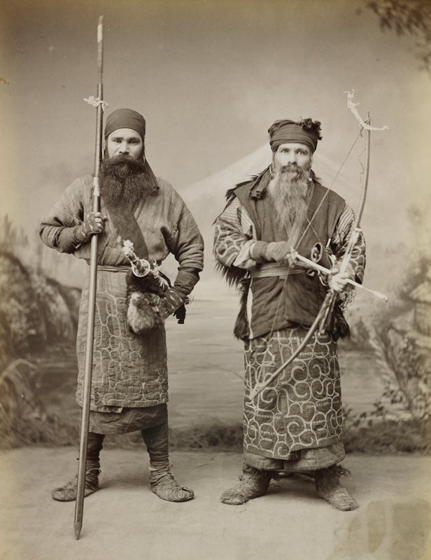 two standing men wearing quilted garments, headscarves, large hoop earrings and wraps on their legs and feet; younger man on left has full dark beard, has a sword at his waist, and holds a long spear; older man on right has full greying bears and holds an arrow in a bow