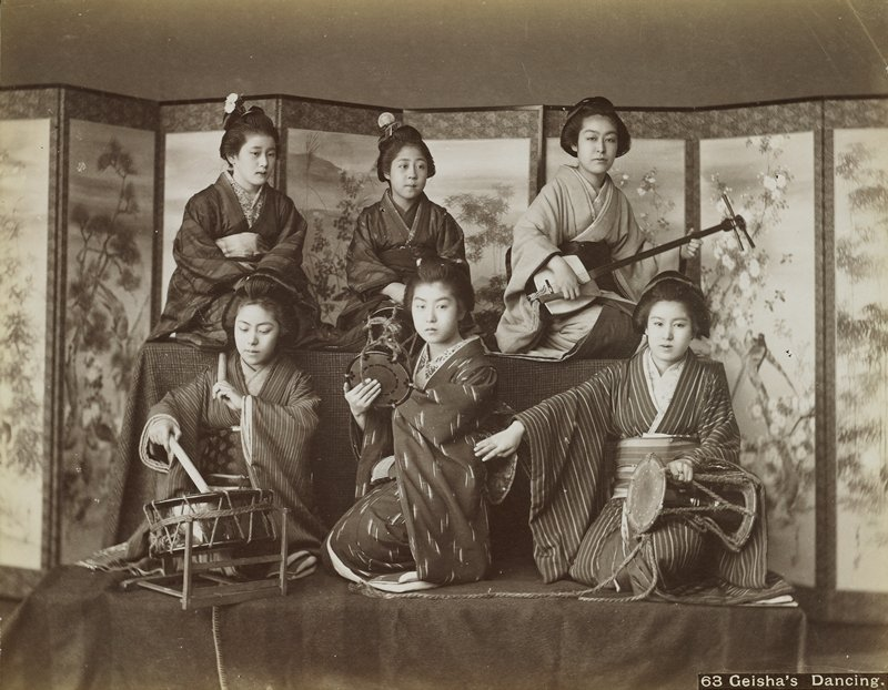 six young women wearing traditional Japanese costumes, seated on two cloth-covered risers in front of folding screens; girl at top right plays a shamisen; three girls at bottom play drums; girl in LRC plays largest drum with large sticks