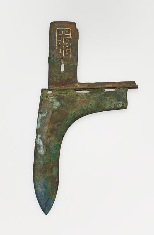 The yuan has narrow, sharpened bevels on both edges and a narrow ridge approximately midway the length of the blade. The nei is rectangular and is decorated on both sides with a rectangular panel displaying a pattern of T forms inlaid with gold. The hu is adorned on the face with two slender birds in gold inlay just opposite the lower slits designed to lash the haft to the Kuo. A third slit occurs at the nei end of the blade, and still another at the base of the gold motif on the nei itself. Patina green and sharp green.
