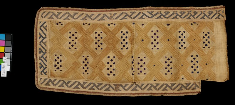 geometric pattern woven tan and blue; cut pile; 2 panel center section; patterned borders on 3 sides dark blue, tan, rust; fourth side plain; approximately 8 1/2 inches at corner of plain side has no lower border - ends are finished