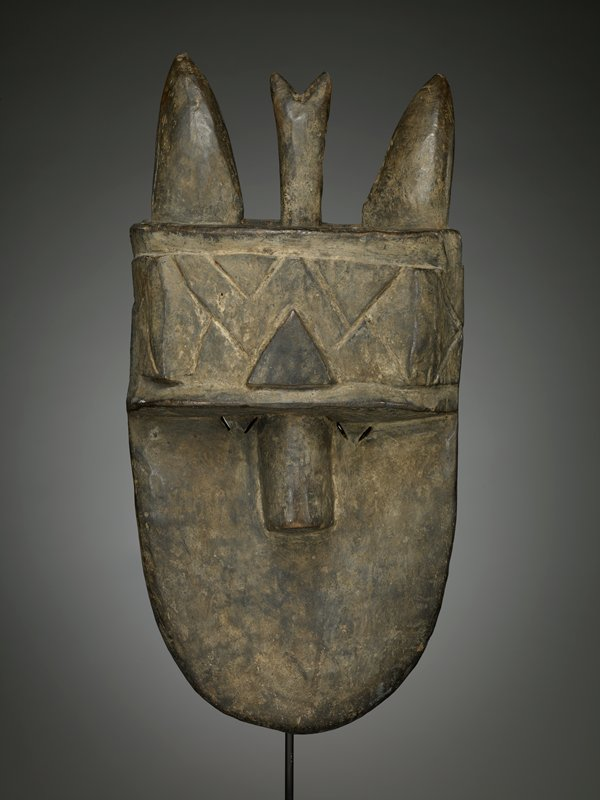 flat face with rounded chin and wedge-shaped, protruding nose; pairs of small diagonal slits for eyes; no mouth; wide headband (or hat) with triangle motifs; pair of pointed vertical horns or ears on top of head, with third forked vertical element between them; dark brown patina
