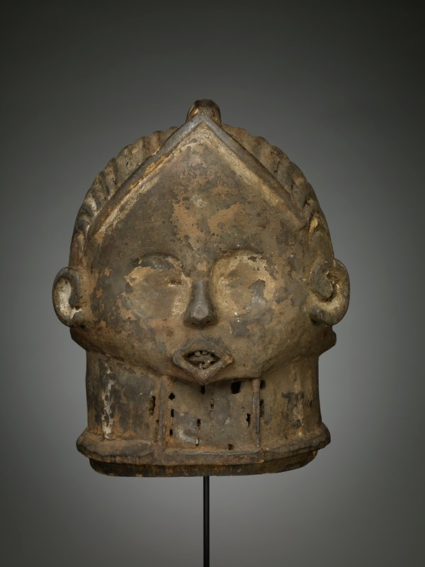 diamond-shaped face; spiraling ears; flat eyes--no eye openings; diamond-shaped open mouth with uneven teeth and tongue; deeply incised ribs form hairstyle, with ridge at top of head and around hairline in front; perforated rectangular element beneath chin; flaky patina with encrustations of white and tan; heavy--thick top section