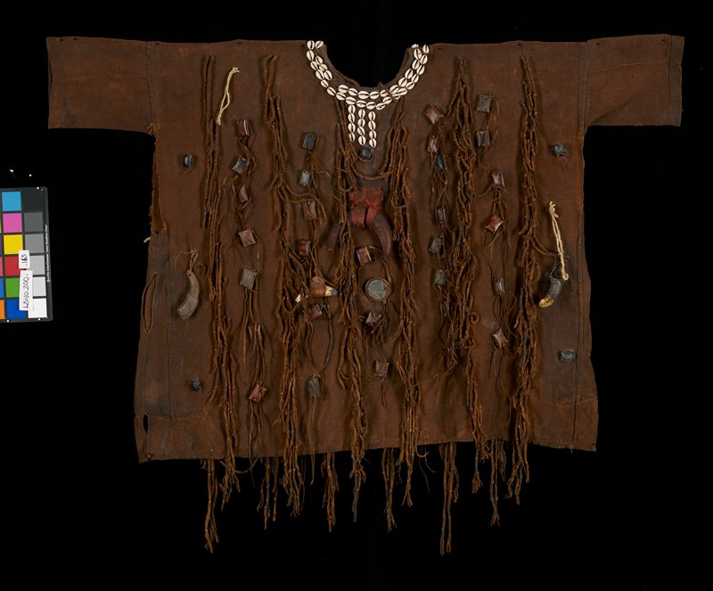 "brown shirt; coarse fabric; short sleeves; sides opening from sleeve seam to approximately 6 1/2 "" down; dreadlocks with rectangular leather covered objects attached; five horn (tusk-like) objects and 1 mirror also attached on one side; four tusk-like objects and 2 mirrors on the other side; 2 rows of shells around neckline; 3 rows of 4 shells at center front; 3 rows 4, 5 and 6 shells respectively at center back"