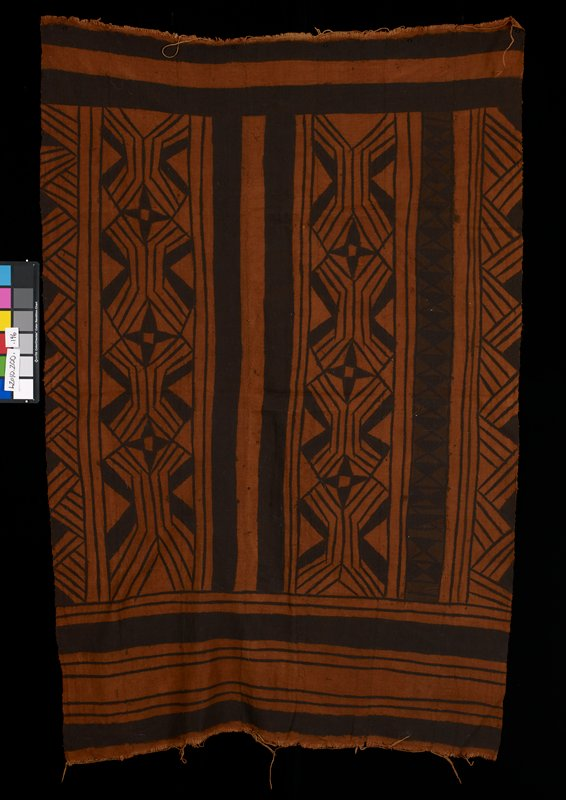 printed seven panel cloth; black pattern on rusty brown ground; printed geometric designs (see L2010.200.197 which is similar but smaller)