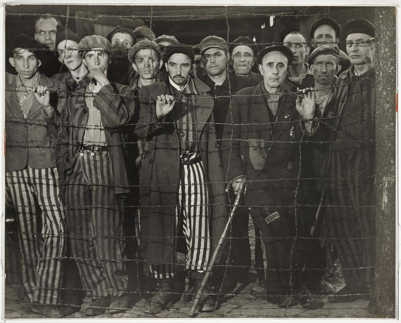 group of men looking out from behind barbed wire; four men wear striped pants and coats; old man at right leans against a cane