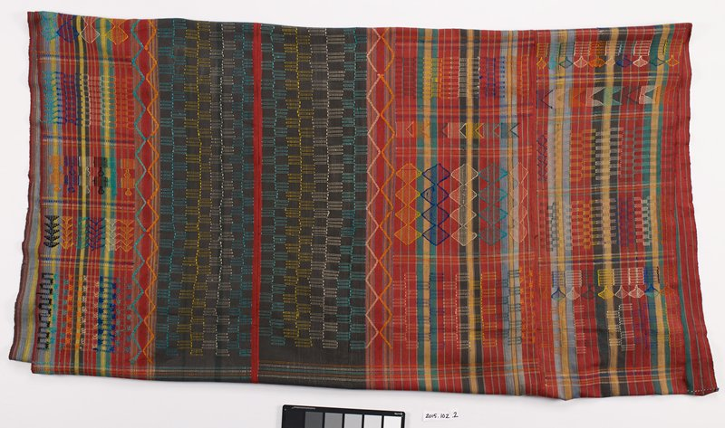 large, multicolored striped cloth with multicolored, abstract embroidered designs; fringe on short ends of fabric is also many colored; cloth consists of 3 panels