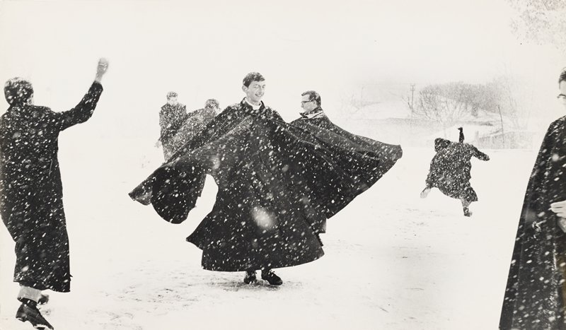 group of priests playing in the falling snow--throwing snowballs and twirling around in their long black cloaks