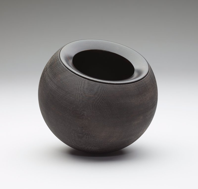 round form with rounded bottom; slightly inward- tapering rim; wide mouth opening; body decorated with incised concentric circles, one on each side and horizontal lines, forming close pattern; dark wood finish