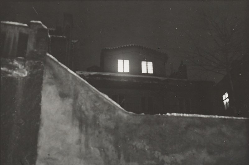 view over a wall, up from low vantage point; two rectangular windows with glowing lights in second story of buildings at center; bare tree at right