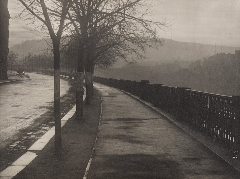 view down a curving path with decorative railing at right; trees on boulevard at left; car at far left in background