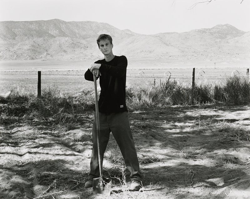 young man wearing dark long-sleeved shirt, pants and boots, with both hands resting on the top of a shovel; mountains in background