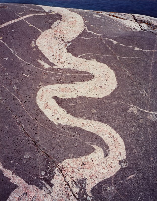 abstract image; wavy off-white line with pink area on grey; cracks; some white lines; water at top